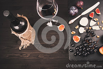 Food background with red wine, figs, grapes and cheese
