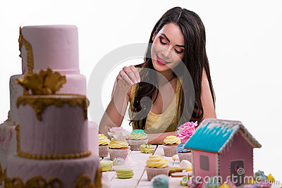Cute girl seasons the confection