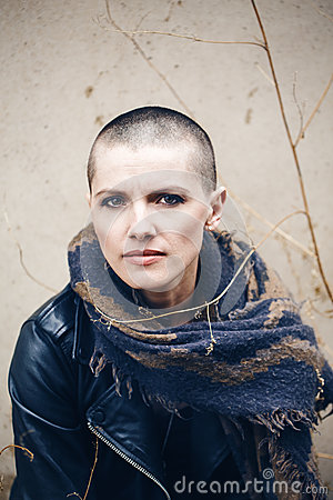 Closeup portrait of sad beautiful Caucasian white young bald girl woman with shaved hair head in leather jacket and scarf