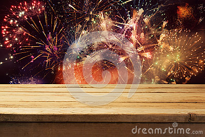 4th of July fireworks background with empty wooden table. Independence day of America