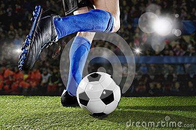 Football player in action running and dribbling at soccer stadium playing match