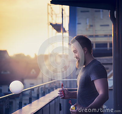 Young man with a beard making soap bubbles with the help of Vaporizers against the evening urban landscape blurred