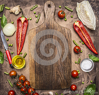 Healthy foods, cooking and vegetarian concept variety of vegetables and fruits are laid out around the cutting board, place for te