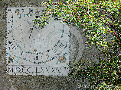 Vertical sundial timepiece of ancient times painted on a wall