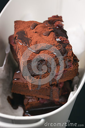 Homemade chocolate sweet brownies cakes with cherry and chocolate sauce or syrup on a dark background