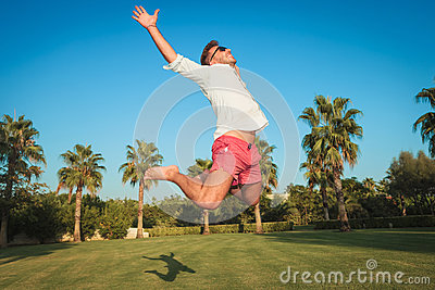 Ecstatic young casual man jumping of joy outside