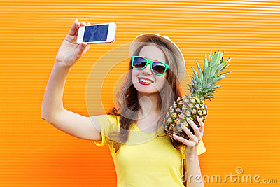 Fashion pretty cool girl in sunglasses, hat with pineapple taking picture selfie on smartphone over colorful