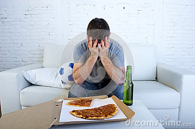 Man with ball pizza and beer bottle watching football game on tv covering eyes sad and disappointed for failure or defeat