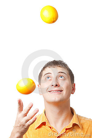 Young adult man juggle with oranges