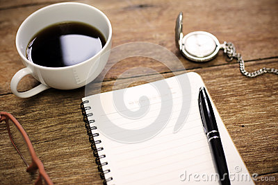 Top view of office table with notebook blank paper pen cup