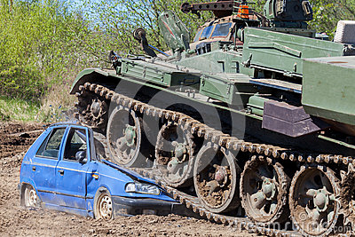 Military tank crushes a blue car