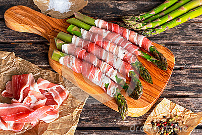 Fresh Organic raw Bacon Wrapped Asparagus on wooden table.