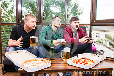 Male friends playing video games, drink beer and have fun at home