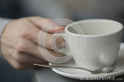 Young man holding cup of coffee  inside the coffee shop