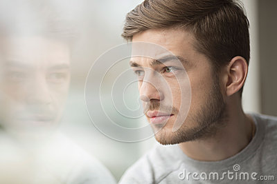 Portrait of thinking young man near glass window. Looking in the window. Reflection from model on the glass.
