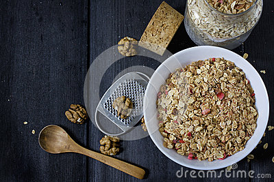 Ingredients for cooking healthy breakfast. Nuts, oat flakes, dried fruits, honey, granola in a white bowl.