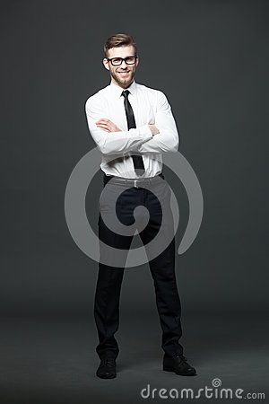 Portrait of handsome young businessman on dark background.