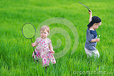 The boy and the girl play on green meadow.