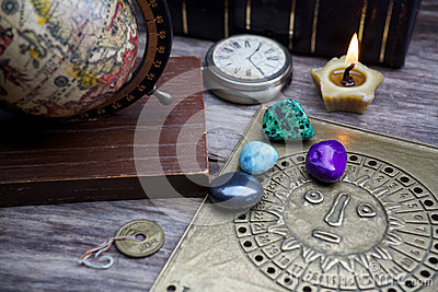 Ancient astrology. Old astrology globe and books with lighting candle