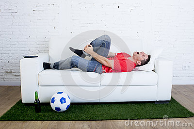 Fanatic football fan lying on couch sofa with ball on green grass carpet emulating soccer stadium pitch mocking player in pain