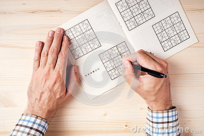 Top view of male hands solving sudoku puzzle
