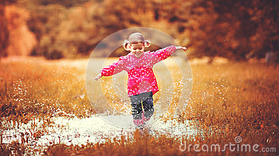Happy child girl running and jumping in puddles after rain