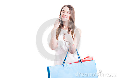 Casual pretty woman with shopping bags calling on mobile phone