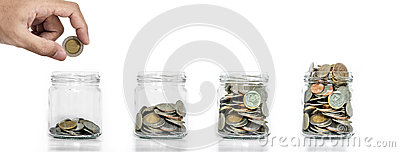 Money saving, Hand putting coin in glass jar with coins inside growing up, on white background