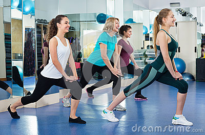 Positive females working out at aerobic class in modern gym