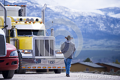 Truck driver going to customized impressive yellow semi truck