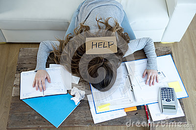 stock image of young woman asking for help suffering stress doing domestic accounting paperwork bills