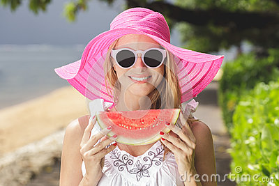 Young beautiful woman with watermelon wearing pink sunhat and su