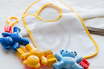 Close up of baby rattle and bib for newborn