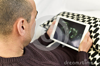 Young man watching a movie or a series in his tablet