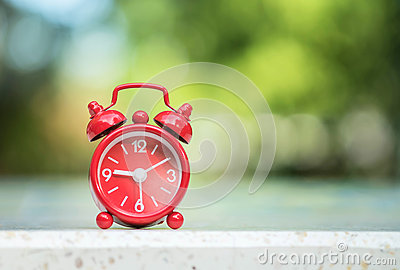 Closeup red alarm clock display seven hours and fifteen minutes on screen on blurred marble desk and park view background
