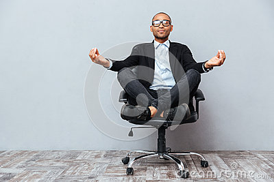 Relaxed african young man sitting and meditating on office chair