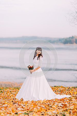 Beautiful innocent thoughtful bride in gorgeous white dress stands on fallen leaves at riverside