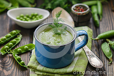 Fresh green pea soup with pea seeds and pea pods