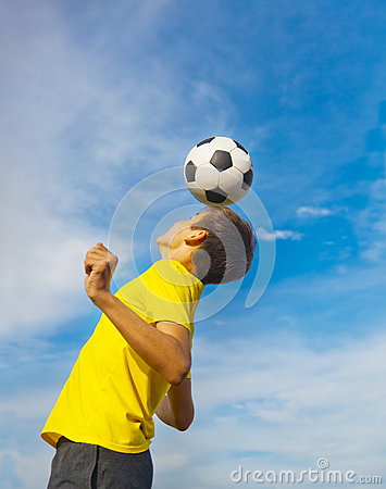 Happy teenage boy with a soccer ball on his head on blue sky bac