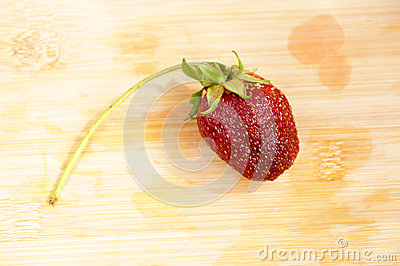 Lonely strawberry on a chopping board