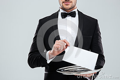 Waiter in tuxedo with bowtie holding blank card on tray