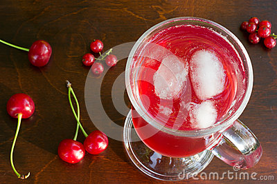 A glass of red cherry juice with ice cubes and cherries and red currants on a wooden background closeup