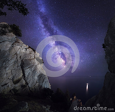 Beautiful colorful night landscape with Milky Way, rocks, sea and starry sky. Mountain landscape. Amazing universe.