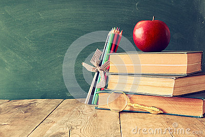 Back to school concept. Blackboard with books and apple