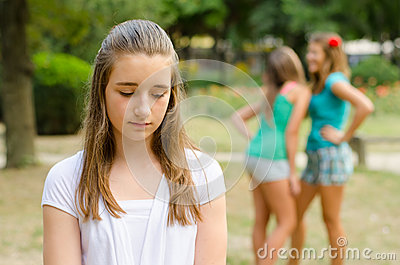 Sad teenage girl rejected by other teenage girls in park