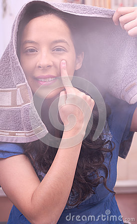 Steam covering all skin face of a woman, spa treatment with a finger in her face