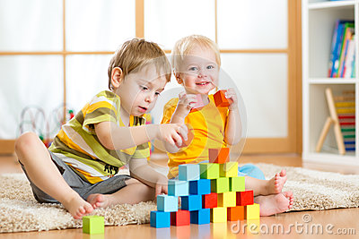 Preschooler children playing with colorful toy blocks. Kid playing with educational wooden toys at kindergarten or day care center