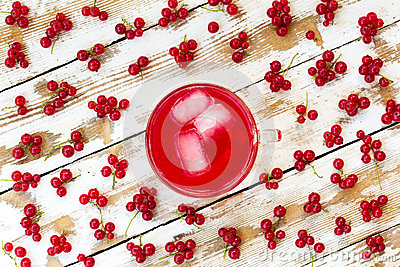 Freshly squeezed red juice with ice cubes and bunches of red currants on a white wooden table with old paint