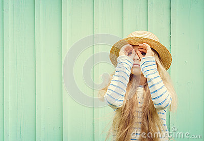 Cute little girl stands near a turquoise wall in boater hat and  looks invented binoculars. Space for text