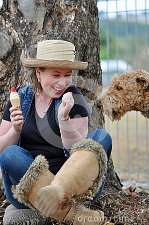 Clever sneaky pet dog sneaking up to pinch ice cream that pretty young girl eating